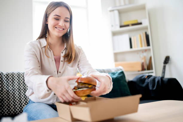 Young woman with take away hamburger at home, coronavirus and food delivery concept. stock photo