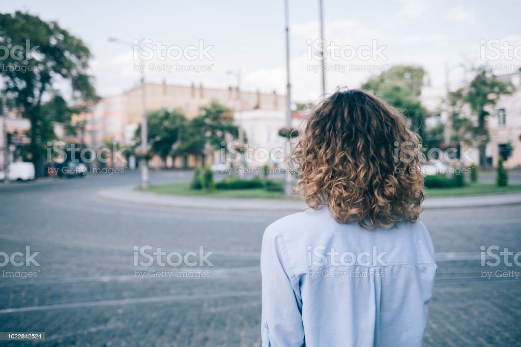 Young woman with thick curly hair looking stock photo