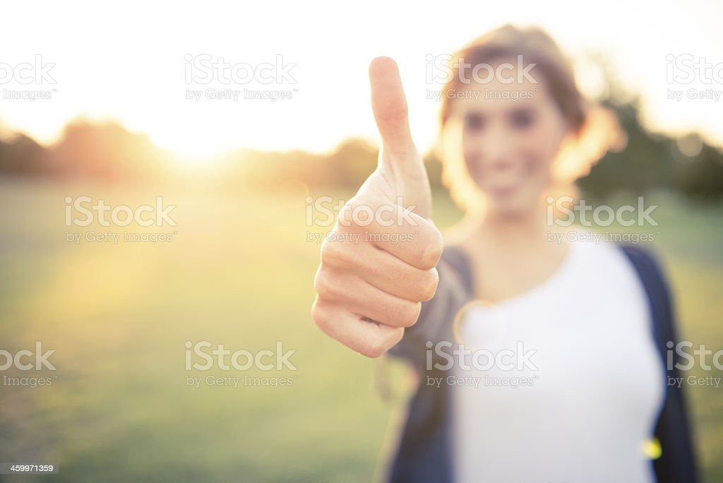 Young italian woman with thumbs up at the park