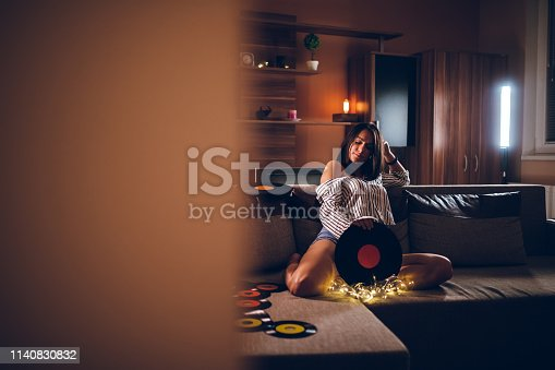Young beautiful caucasian woman playing old records.