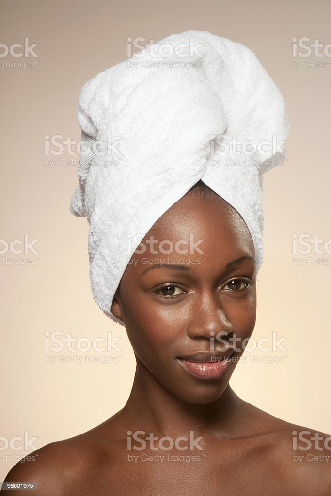 Young woman with towel wrapped around hair foto stock royalty-free