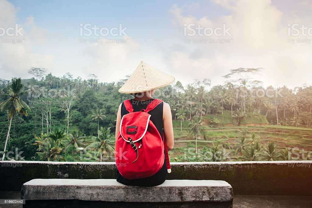 Young woman with traditional Asian hat sitting near rice field stock photo