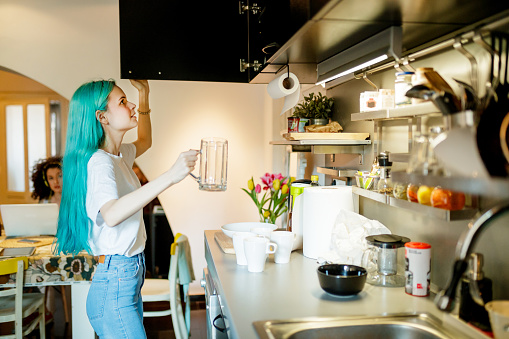 Young woman with turquoise hair with coffee can looking for spoon by kitchen sink