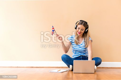 istock Young woman with UK flag using a laptop computer 1094263388