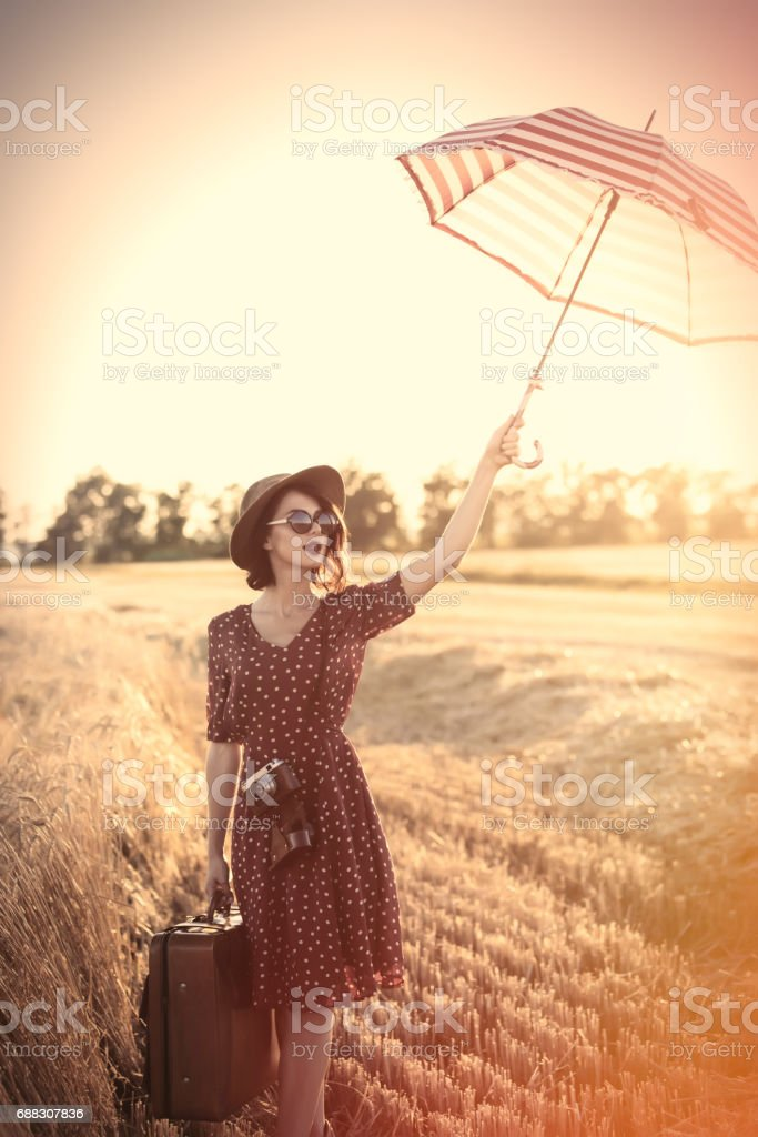 young woman with umbrella and suitcase - foto de acervo