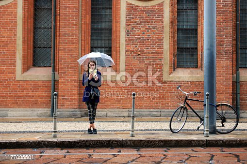 Young woman with umbrella using smart phone and waiting