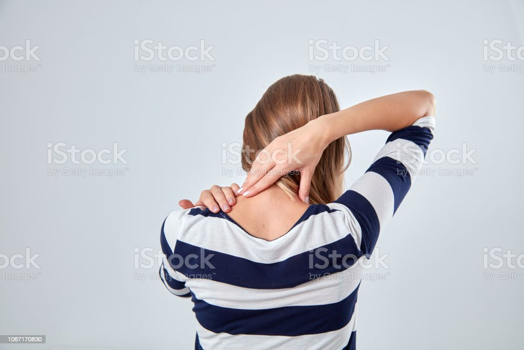 Young woman with upper back pain holding spine.