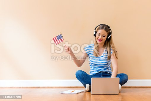 istock Young woman with USA flag using a laptop computer 1145097788