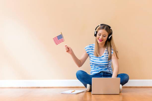 Junge Frau mit USA-Flagge mit einem Laptop – Foto