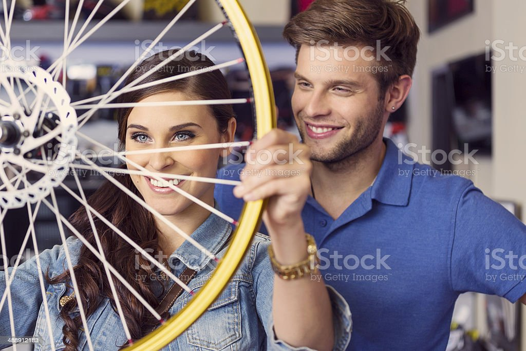 Young woman with wheel Close up of happy young woman holding a bicycle wheel in bike store with her boyfriend or sales clerk standing behind her.  20-24 Years Stock Photo