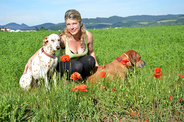 Young woman with white and brown dog on green meadow - foto de stock