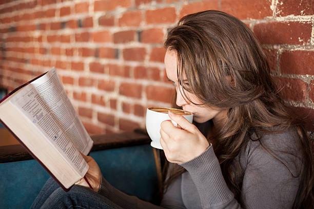 Junge Frau mit weißen Kaffeetasse liest die Bibel – Foto