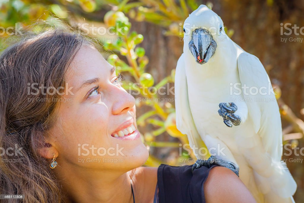Young woman with white parrot sitting on her shoulder stock photo