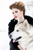 Young woman with wolf dog in snow
