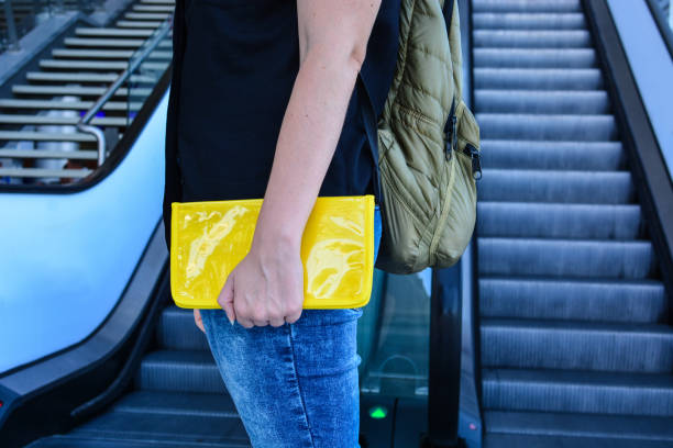 Young woman with yellow travel case, passenger in airport stock photo