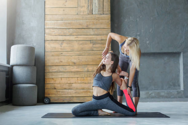 Young woman with yoga instructor in fitness club, mermaid pose stock photo