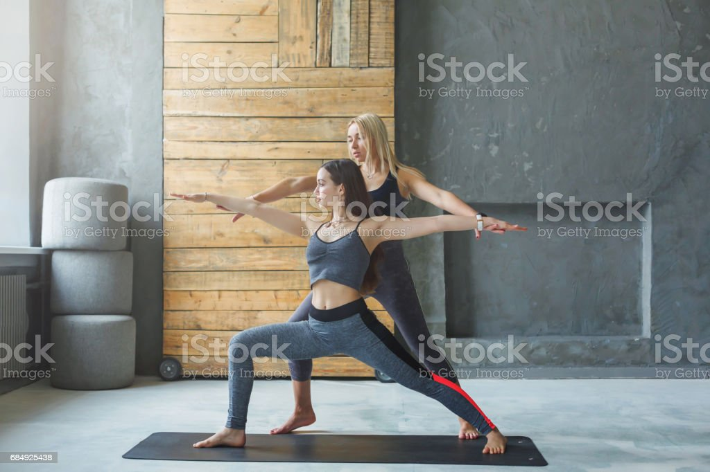 Young woman with yoga instructor in fitness club, warrior pose stock photo