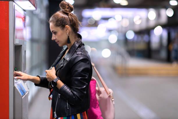 Junge Frau zieht Geld an einem Geldautomaten ab – Foto