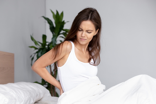 istock Young woman woke up feels pain in lower back 1150540103