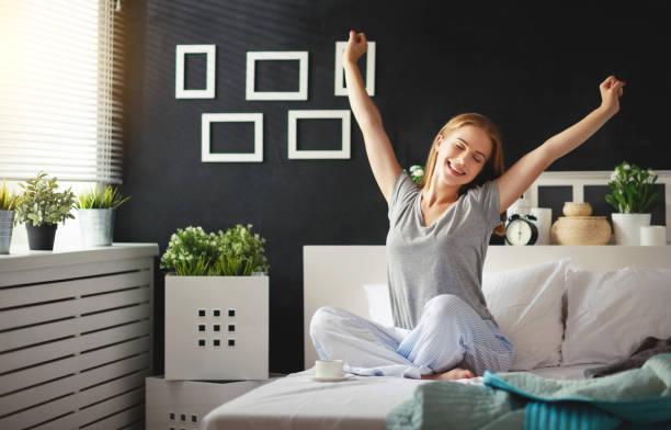 jovem mulher acordou de manhã no quarto pela janela de costas - foto de acervo