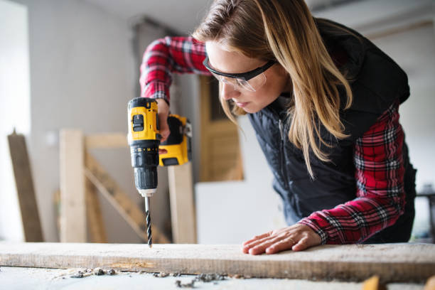 Young woman worker in the carpenter workroom. Young woman worker in workroom. Female carpenter using drill. drill stock pictures, royalty-free photos & images