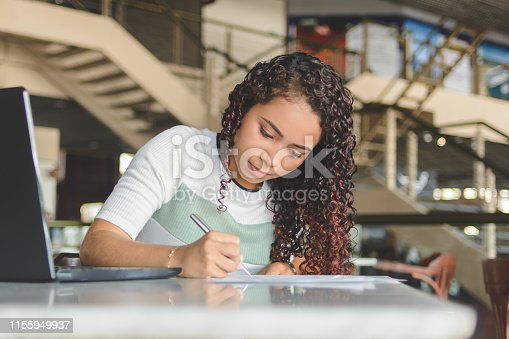 Young woman worker or student working with laptop making notes or filling forms