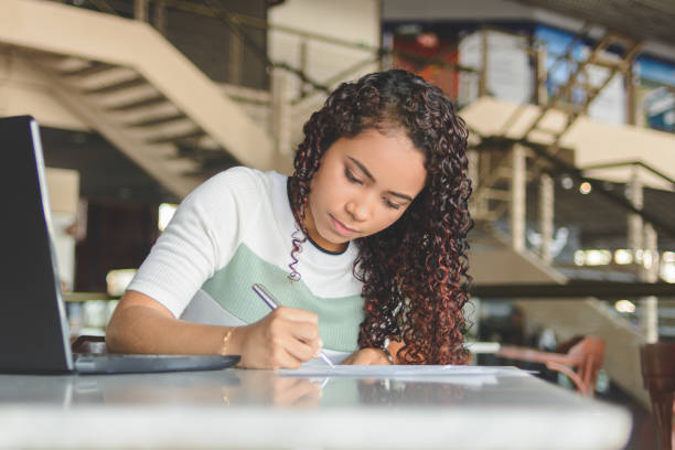 Young woman worker or student working with laptop making notes or filling forms stock photo