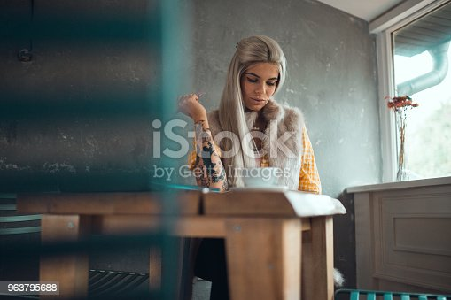 1183295518 istock photo Young woman working and writing in the coffee bar indoors 963795688