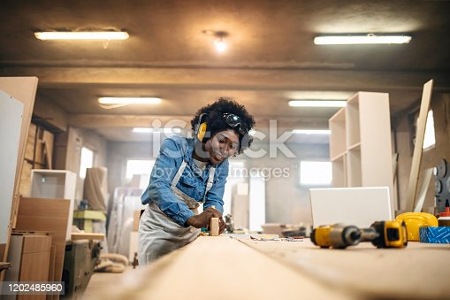 One African-American female carpenter working with wood in her workshop.