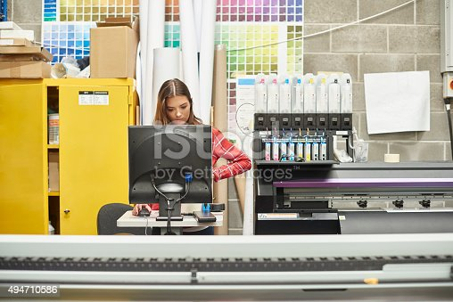 A young woman is working on a digital printing machine . she is at the computer terminal loading in the next print job .