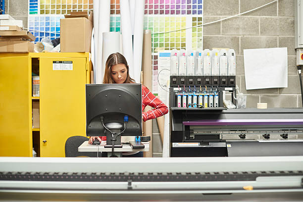 young woman working at a digital printing company A young woman is working on a digital printing machine . she is at the computer terminal loading in the next print job . printing plant stock pictures, royalty-free photos & images