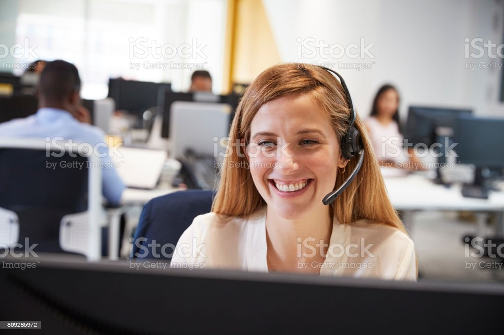 Young woman working at computer with headset in busy office stock photo