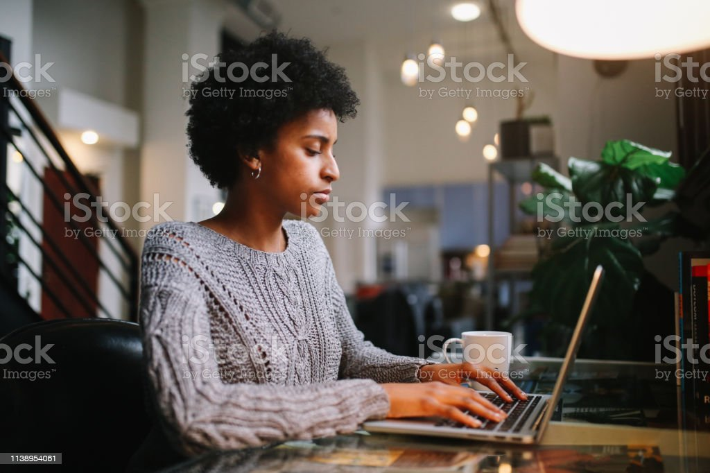 young woman working at her home in Los Angeles, California Young mixed race woman sitting at the desk in her apartment in downtown Los Angeles, typing at the laptop, finishing up her freelancer work or studies while having a coffee. 20-29 Years Stock Photo