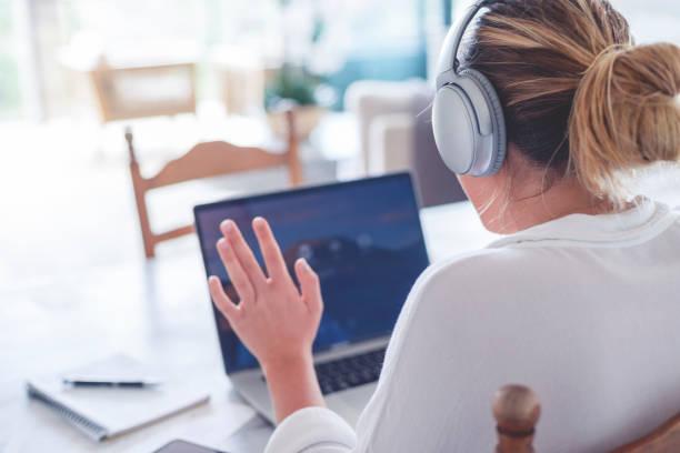 Junge Frau arbeitet zu Hause auf einem Videoanruf. Sie winkt der anderen Person auf dem Anruf – Foto