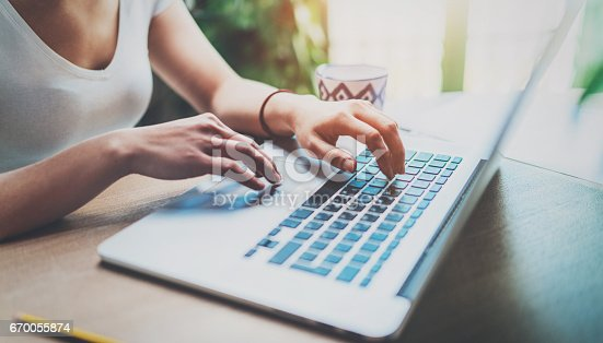 istock Young woman working at home on modern computer while sitting at the wooden table.Female hands typing on laptop keyboard.Concept of young modern people using mobile devices at home.Blurred background. 670055874