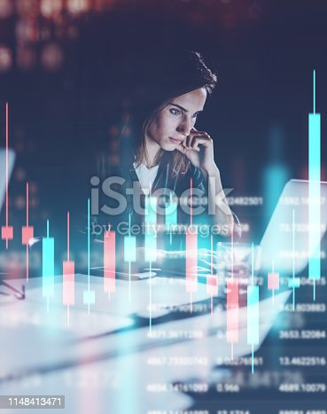 istock Young woman working at night modern office loft.Red and green candlestick chart and stock trading on background. Double exposure. 1148413471