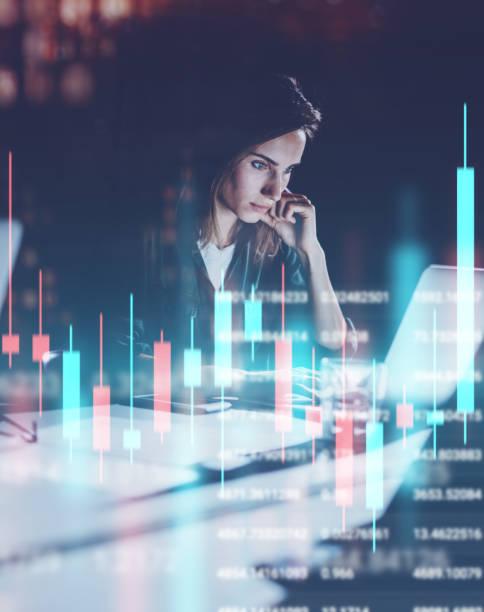 Junge Frau arbeitet in der Nacht modernen Büroloft. Rote und grüne Kerzenständer und Aktienhandel auf dem Hintergrund. Doppelte Belichtung. – Foto