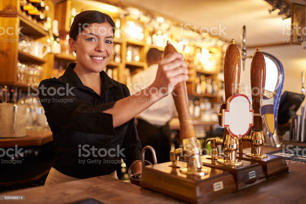 A young woman working behind a bar looking to camera, horizontal stock photo