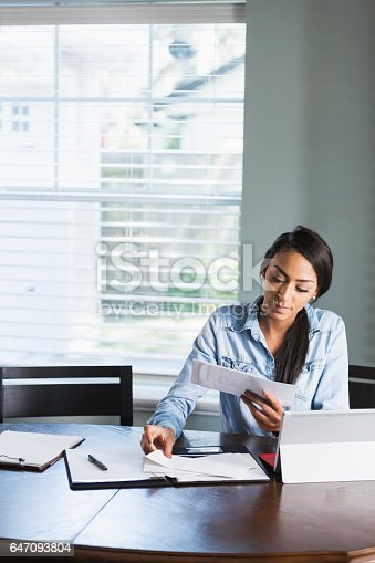 istock Young woman working from home or paying bills 647093804