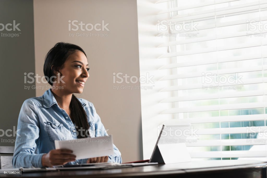Young woman working from home or paying bills stock photo