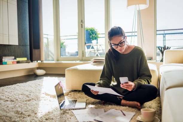 young woman working from home young woman sitting on the floor of her living room and working working from home photos stock pictures, royalty-free photos & images