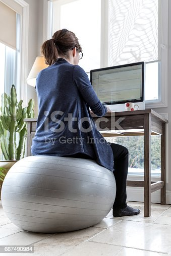 Young Woman Working From Home And using a fitness ball as chair