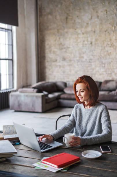 Junge Frau in ein Loft-Apartment mit einem Laptop arbeiten – Foto
