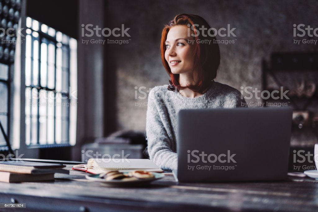 Young woman working in a loft apartment with a laptop computer stock photo