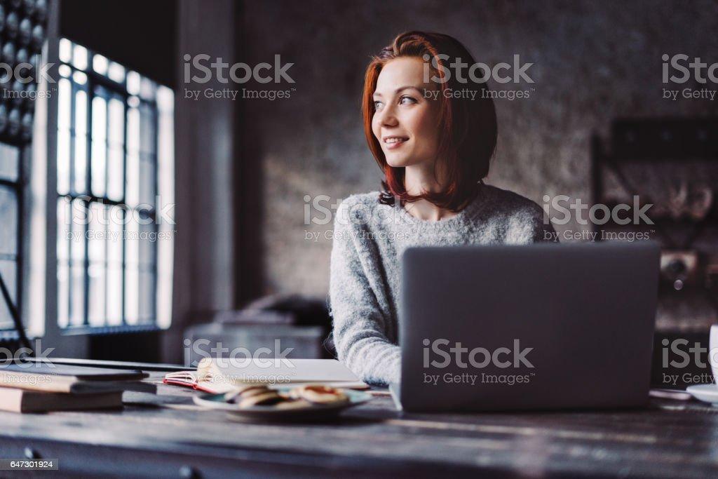 Ung kvinna som arbetar i en Loftlägenhet med en bärbar dator bildbanksfoto