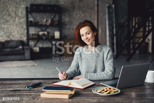 Young woman using laptop in a loft apartment