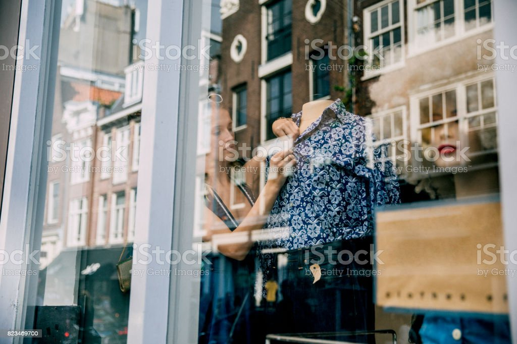 Young Woman Working in a Shop Window stock photo
