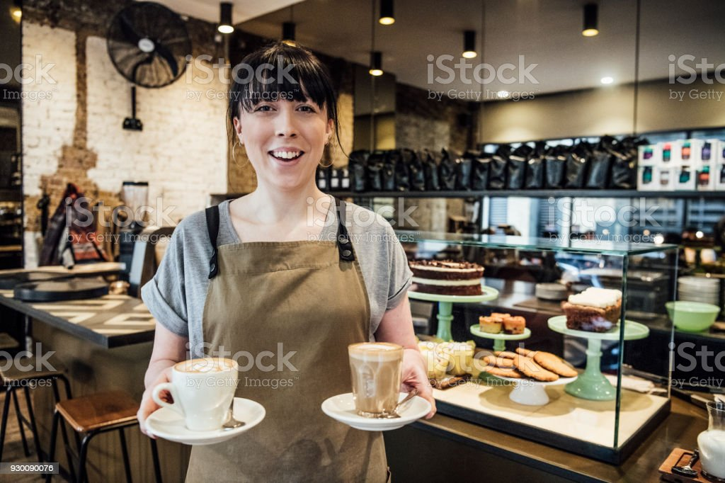 Young woman working in cafe with hot drinks stock photo