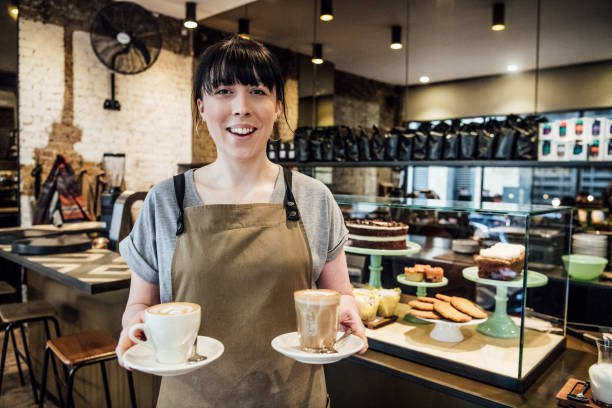 Young woman working in cafe with hot drinks Female barista in her 20s serving coffee in cafe with cakes on display in background barista stock pictures, royalty-free photos & images
