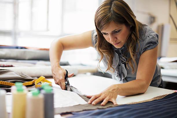 giovane donna che lavora in abiti produzione - tailor working foto e immagini stock